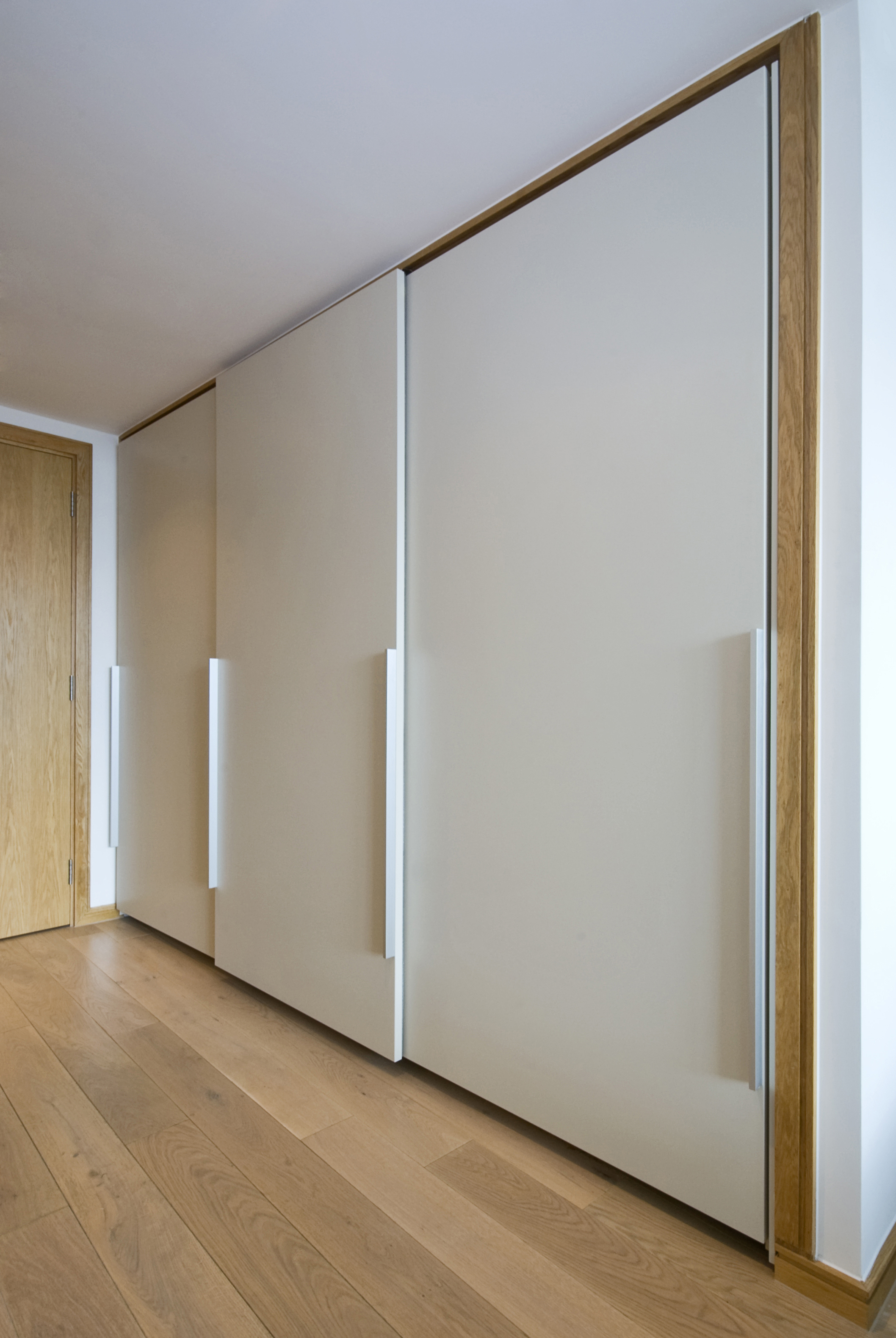 Framless fitted sliding wardrobes with matt finish painted lacquered panels