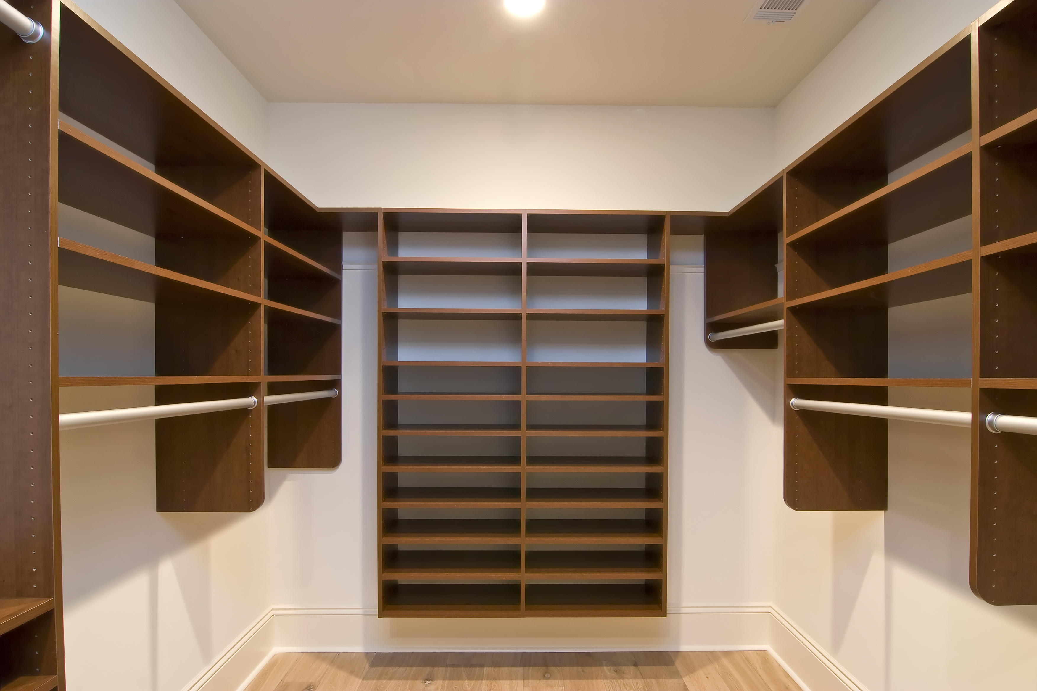 Unique fitted walk in wardrobes with a perfect layout consiting of floating shelves and combination of long hanging rails to achieve maximum storage